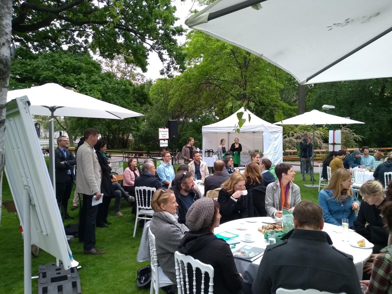 """TeilnehmerInnen sitzen rund um """"Runde Tische"""" beim """"Forum im Park"""""""